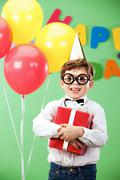 Portrait of happy lad in funny eyeglasses on birthday party with present Stock Photos