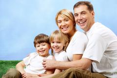 portrait of joyful family looking at camera and laughing - stock photo