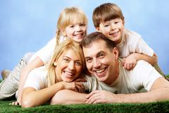 Photo of family members smiling at camera on blue background Stock Photos
