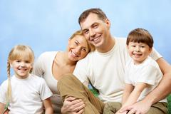 portrait of joyful family looking at camera on blue background - stock photo