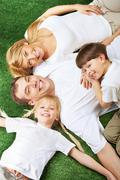 above view of family members lying on green grass and smiling at camera - stock photo