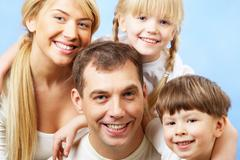 faces of family members smiling at camera on blue background - stock photo