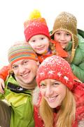 Happy family in winter clothes looking at camera and smiling Stock Photos