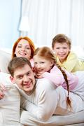 Portrait of happy parents and their children relaxing on the sofa at home Stock Photos