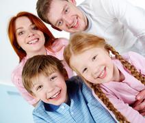 Onnellinen pari ja heidän kaksi lasta hymyilee kun katsot kameraa Kuvituskuvat