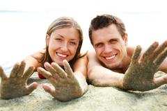 Photo of smiling couple lying on beach and showing their hands covered with sand Stock Photos