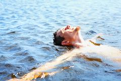 Delighted guy bathing in water and enjoying it Stock Photos