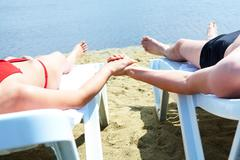 Image of two people lying on deck chairs and sunbathing on resort Stock Photos