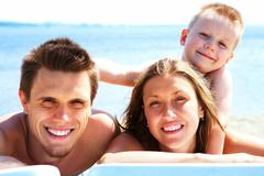 photo of smiling family looking at camera while sunbathing - stock photo