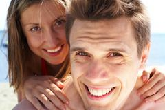 Photo of smiling guy looking at camera while pretty woman behind embracing him Stock Photos