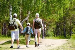 rear view of three family members going down country road at summer - stock photo