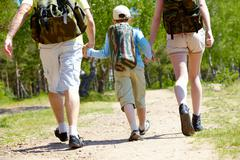 rear view of three family members going down forest path during summer vacation - stock photo