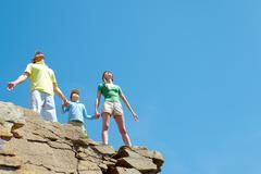 Portrait of family members standing on cliff with stretched arms and enjoying ho Stock Photos