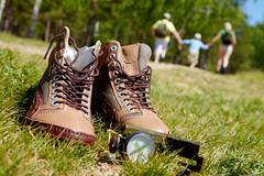 image of pair of boots and compass on background of happy family running down gr - stock photo