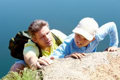 Image of man helping his son to climb rock on background of water outdoors Stock Photos
