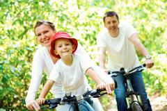 portrait of happy woman with son riding a bicycle in park on background of male - stock photo