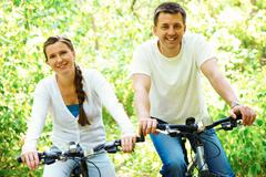 Photo of happy husband and wife riding bicycles outdoors Stock Photos