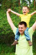 portrait of father holding his son on shoulders during summer vacation - stock photo