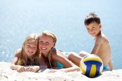 Photo of happy family lying on sand by water during summer vacation Stock Photos