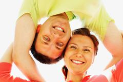 Below angle of cheerful couple looking at camera while on summer vacation Stock Photos
