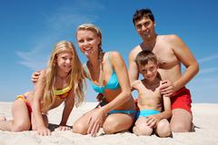 Photo of happy family sitting on sand on summer vacation Stock Photos