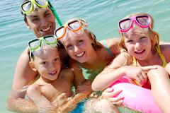 Stock Photo of portrait of cheerful family in aqualungs looking at camera from water