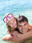portrait of cheerful girl embracing her father and looking at camera from water - stock photo