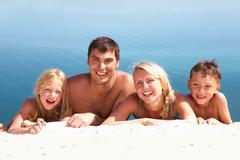 photo of happy family lying on sand on background of blue water - stock photo