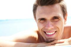 Photo of smiling guy looking at camera while sunbathing Stock Photos