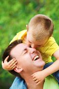 portrait of father cuddling his son during summer vacation - stock photo