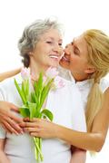Stock Photo of portrait of pretty woman embracing her senior mother and holding tulips