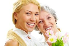Stock Photo of portrait of happy woman and her senior mother looking at camera