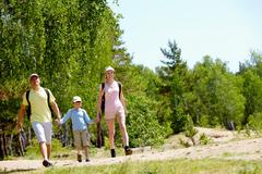 Portrait of happy family walking down countryside at summer Stock Photos