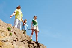 Stock Photo of portrait of family members standing on cliff with stretched arms and enjoying ho