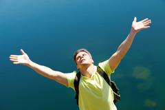image of man with stretched arms on background of water outdoors - stock photo