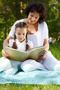 portrait of mother and daughter reading in park on summer day - stock photo