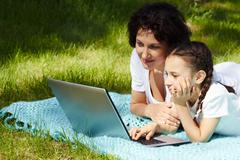 Portrait of mother and daughter looking at laptop screen in park on summer day Stock Photos
