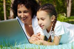 Stock Photo of portrait of mother and daughter looking at laptop screen on summer day
