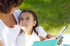 Stock Photo of portrait of curious girl looking at her mother while discussing book in park