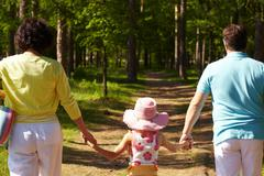 Back view of parents and their daughter walking in the forest on summer day Stock Photos