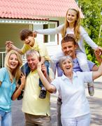Stock Photo of portrait of senior and young couples with children outdoors by their cottage