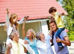 portrait of happy senior and young couples having fun with children outdoors by - stock photo