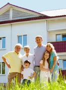 Stock Photo of portrait of happy senior and young couples standing outdoors with new cottage at