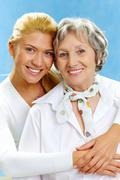 Portrait of attractive daughter hugging mother on a blue background Stock Photos