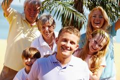 portrait of happy senior and young couples looking at camera during vacation wit - stock photo