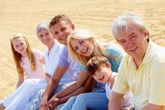 happy family sitting on sand and looking at camera - stock photo