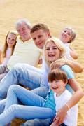 Happy family sitting on sand and looking at camera Stock Photos
