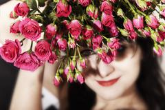 Stock Photo of brunette woman with a bouquet of pink roses