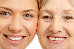 close-up of two faces of beautiful woman and mother - stock photo