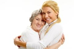Portrait of attractive girl and senior woman embracing each other Stock Photos